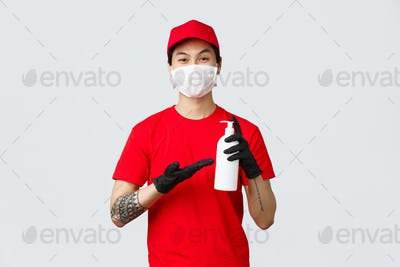 Smiling asian delivery man in red uniform and medical mask, gloves. Courier showing hand sanitzer