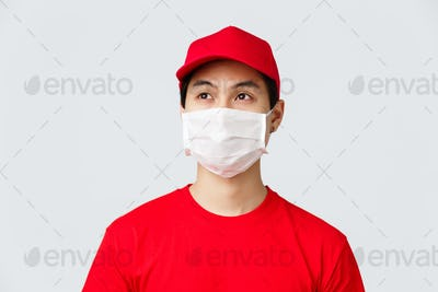 Covid-19, self-quarantine online shopping and delivery concept. Thoughtful young asian courier