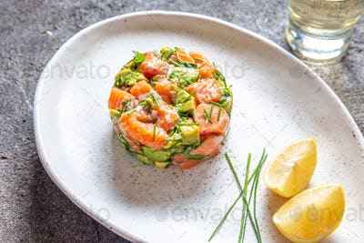 Peruvian nikkei food. Salmon avocado ceviche on black plate, black background top view