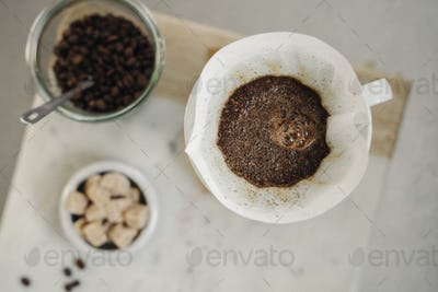 Making filter coffee. Overhead view of ground coffee, paper filter and sugar lumps.