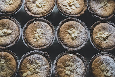 High angle view of freshly baked tarts topped with flaked almonds and icing sugar.