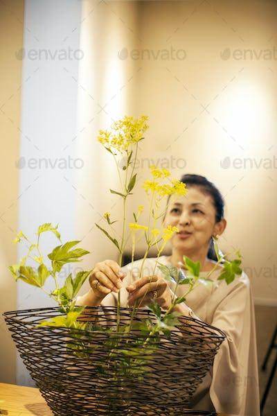 Japanese woman standing in flower gallery, working on Ikebana arrangement.