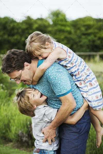 A father and two children in a garden, a boy hugging him around the waist and a girl on his back