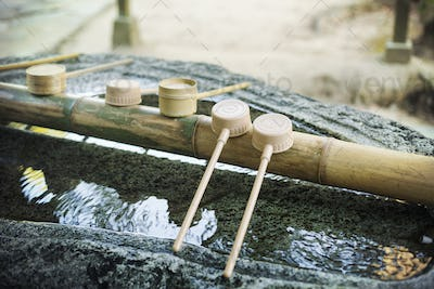 Close up of bamboo water hand washing basins at Shinto Sakurai Shrine, Fukuoka, Japan.