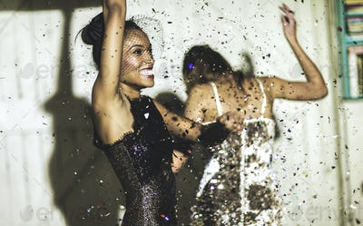 Two women wearing cocktail dresses at a party dancing in a shower of glitter confetti.