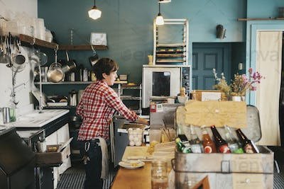 A woman working behind the counter in a coffee shop.