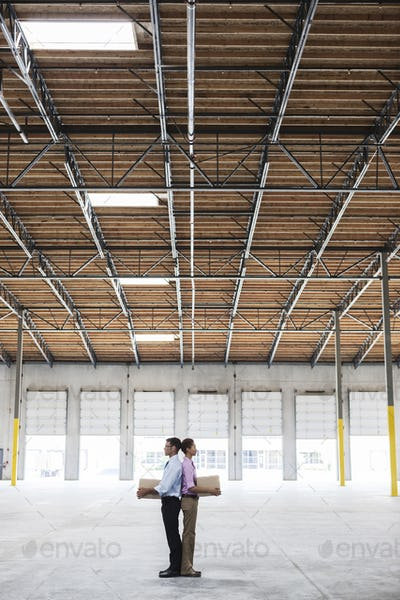 Caucasian man and black female holding cardboard boxes in middle of empty warehouse interior.