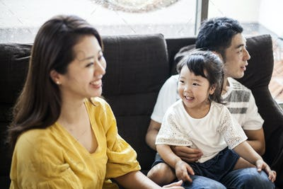 Portrait of smiling Japanese man, woman and young girl sitting on a sofa.