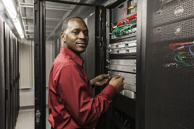 Black man technician working on computer servers in server farm.