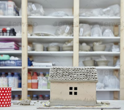 Shelves and pottery in a pottery studio, and a clay cottage on the workbench.