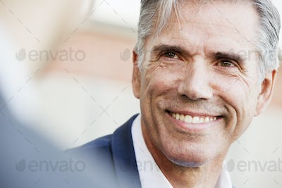 A man in a white shirt with grey hair, smiling, his head turned to speak to another person.