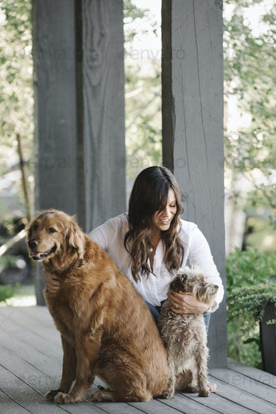 A woman on a porch patting her two dogs.