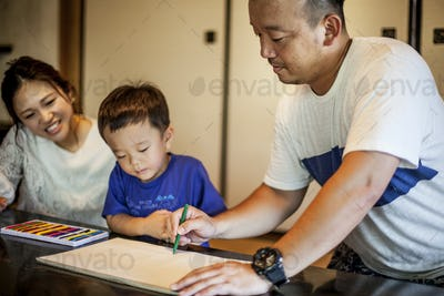 Japanese woman, man and little boy sitting at a table, drawing with colouring pens.