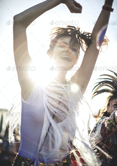 Young woman at a summer music festival arms raised, dancing among the crowd.