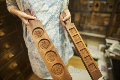 A small artisan producer of specialist treats, sweets called wagashi. A woman holding shaped wooden