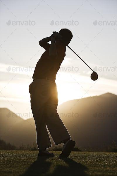 Senior golfer teeing off at sunset.