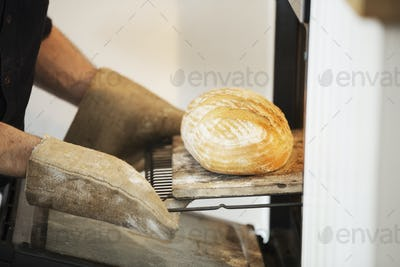 Close up of a baker taking a freshly baked loaf bread out of an oven.