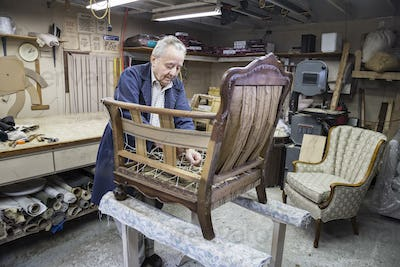 Senior Caucasian man upholsterer working on an antigue chair in his garage shop.