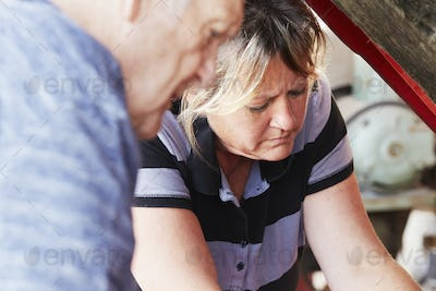 Mature woman and senior man repairing a car, looking under bonnet.