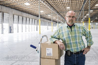 Caucasian male standing next to hand truck in front of loading dock doors inside of a new warehouse.