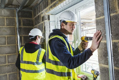 Two workmen on a construction site, builder in hard hat using an electric drill on a window frame.