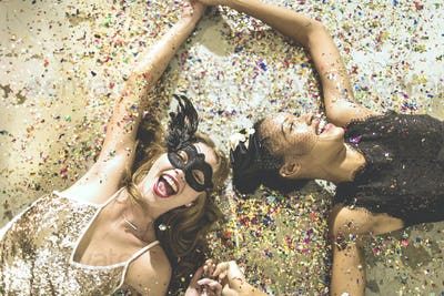 Two young women lying on a carpet surrounded by fallen confetti.