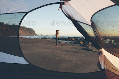 Man framed by camping tent, standing on beach and looking through binoculars at dusk, Olympic
