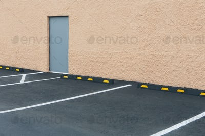 A car park with lined bays outside a building, and a door in a wall.