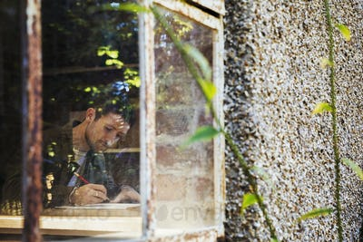 View through a window of a young man drawing in a notebook, a designer at work.