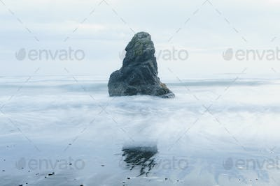 Rock formation on the coastline, exposed on the beach at low tide.