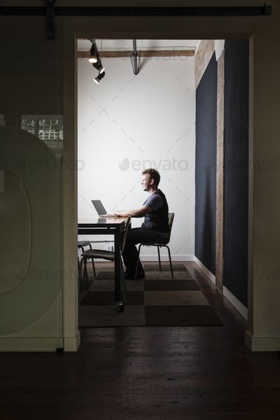 Caucasian male worker using a laptop computere at a conference room table