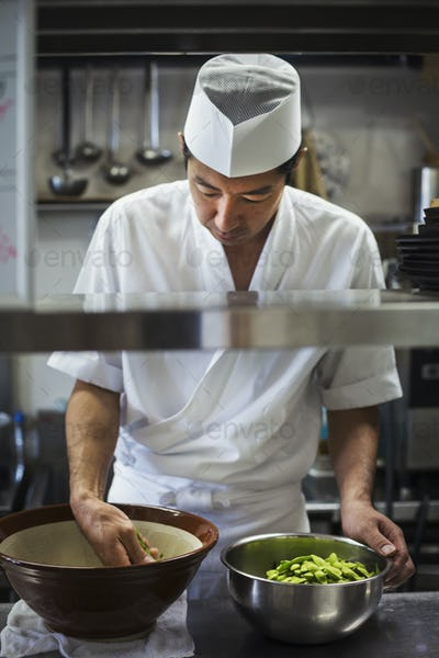 Chef working in the kitchen of a Japanese sushi restaurant, preparing bowl of edamame beans.