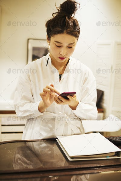 Woman working in a fashion boutique in Tokyo, Japan, using mobile phone.