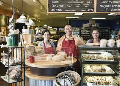 Hispanic man baker and his employees at the bakery.