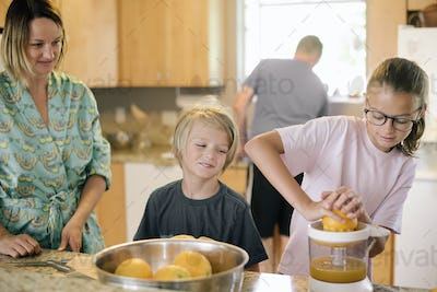 Family preparing breakfast in a kitchen, girl squeezing oranges.