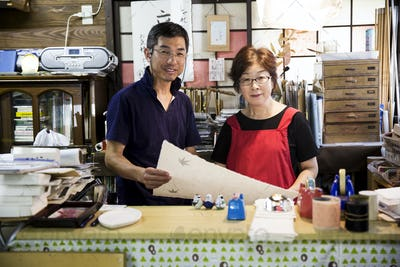 A man and woman, partners in a traditional business,  behind a counter in a shop, displays of