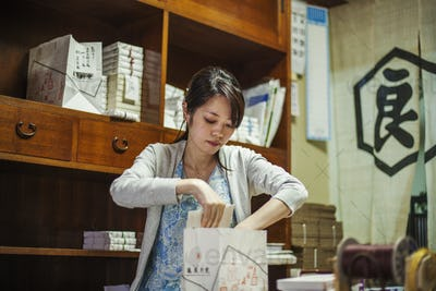A small artisan producer of specialist treats, sweets called wagashi. A woman working packing sweet