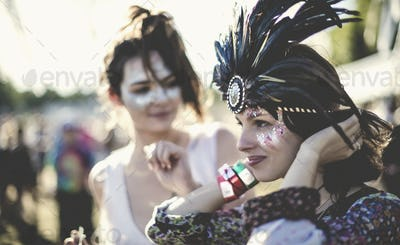 Two young women at a summer music festival faces painted, wearing feather headdress.