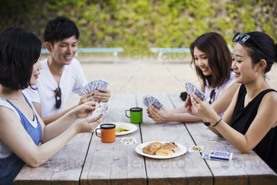 Three young women and a man sitting at a table, playing cards.