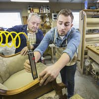 Young Caucasian man learning the art of upholsery from a senior male upholsterer.