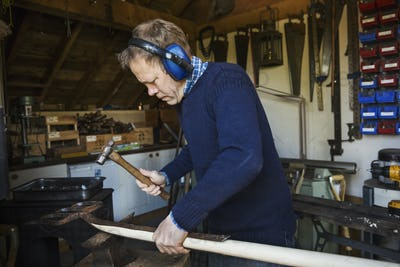 Man standing in a workshop, wearing ear protectors, holding a hammer, working on a piece of wood.
