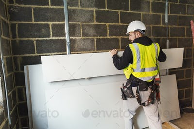 A workman in hard hat and high vis jacket stacking wood against a wall at a construction site.