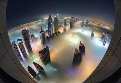 Aerial view of cityscape with illuminated skyscrapers above the clouds in Dubai, United Arab