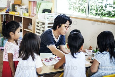 Male teacher talking to group of children at a table in a Japanese preschool.