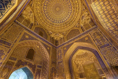 Interior, the blue and yellow glazed walls and dome of a Madrasa building in Samarkand.
