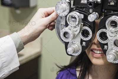 Ophthalmologist using a phoropter instrument to adjust an eyeglass perspection for a patient.