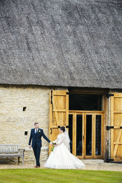 A bride and groom on their wedding day, walking hand in hand from a barn.