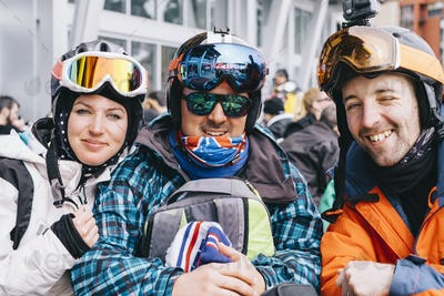 Three people, a young woman and two men in ski gear, in a row On a ski-ing holiday.