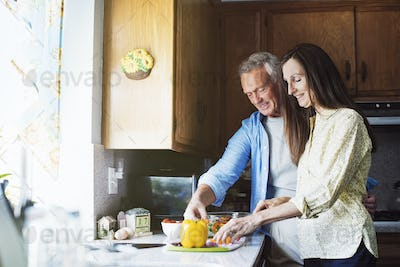Smiling senior couple standing in a kitchen, preparing food.