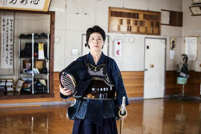 Female Japanese Kendo fighter standing in a gym, holding Kendo mask and sword, looking at camera.